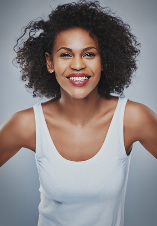 upper half: Front centered view on happy young Black female with enthusiastic expression leaning forward over gray background Stock Photo