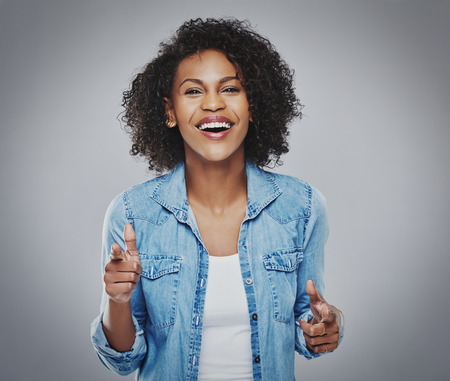 Single gorgeous woman in curly hair wearing white blue denim shirt singing and gesturing with fingers over gray background Stock Photo