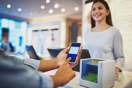 店の女性レジ係の笑顔として登録の前に携帯電話で情報を入力お客様の指にビューをクローズ アップ