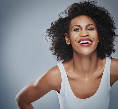 leans: Single laughing young Black adult female in sleeveless undershirt with happy expression leaning forward over gray background and copy space Stock Photo