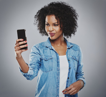 blue collar: Cute single young woman with curly hair and blue collar shirt taking picture or self-portrait with phone over gray background