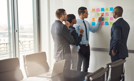 business partnership: Diverse group of four business people gathered around white board with sticky notes planning something