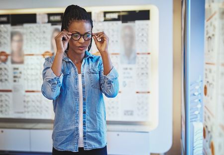 eye wear: Single beautiful young adult African-American female in blue shirt testing the fit for eyeglasses on her head in eye wear shop