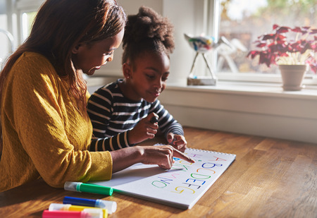 Woman and child learning alphabet at home, black mother and daughter