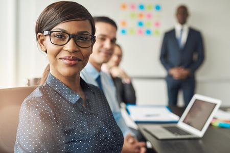 Alegre hermosa mujer usando anteojos profesionales sentados con los compañeros de trabajo masculinos y líder del equipo en la sala de conferencias en el trabajo