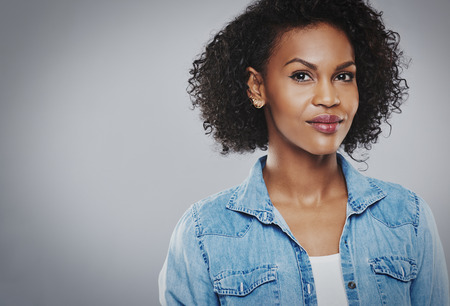 Confident beautiful black woman with blue jean shirt on gray background Фото со стока