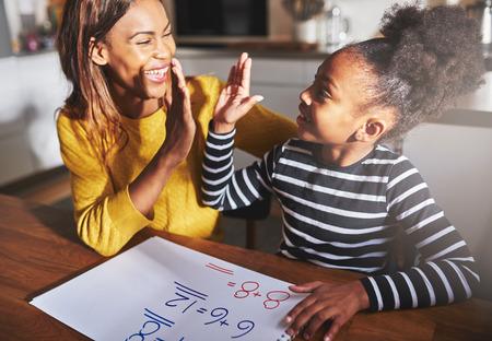 Leren om te berekenen, high five succes, zwarte moeder en kind