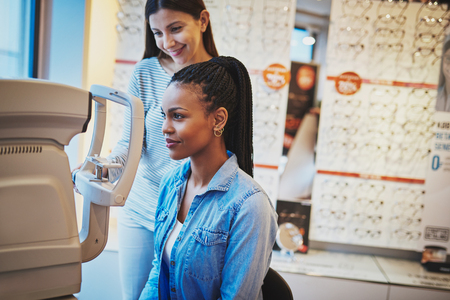 Serious black woman with ponytail and wearing blue jean shirt takes eye exam in optical shop Stock Photo