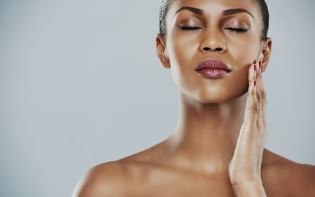 glowing: Close up of beautiful serene African bare shouldered female with eyes closed and hand on cheek over gray background with copy space on one side