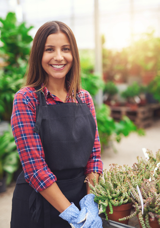 saleslady: Smiling young employee in a flower nursery standing at a display of succulents in the greenhouse giving the camera a friendly smile Stock Photo