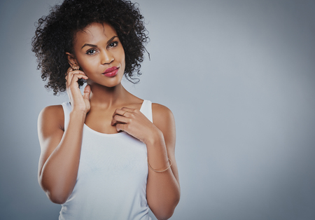 undershirt: Single gorgeous Black woman in white sleeveless undershirt with serious expression holding neck with hand over copy space