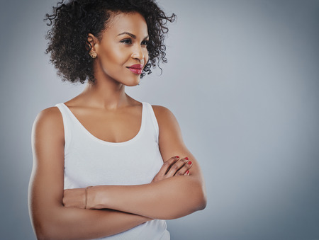 sanguine: Single African woman with beautiful confident smile looking toward copy space and folded arms over gray background