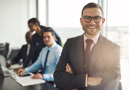 Confident smiling business executive with folded arms near conference table with three co-workers discussing something in large bright office room