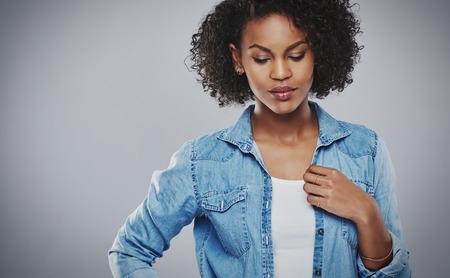 mujeres tristes: mujer afroamericana bastante pensativa con un peinado afro rizado de pie con su mano a su pecho mirando hacia abajo en el suelo con una expresión seria considerado, en gris con espacio de copia
