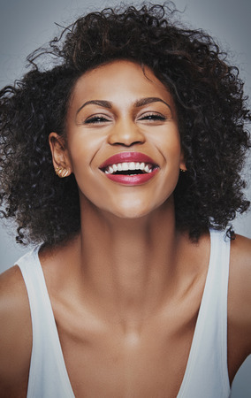 undershirt: Front close up view on laughing young Black woman in sleeveless undershirt with joyful expression leaning forward over gray background