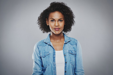 women face stare: Serious beautiful black woman with blue jean shirt on gray background Stock Photo