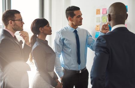 Multiraciale groep van ondernemers staan bespreken kleurrijke memo's op een muur in een concept van teamwork en samenwerking