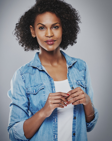 american content: Calm woman wearing red nail polish and blue jean shirt against gray background Stock Photo