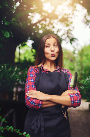 jaunty: Sassy playful young woman pouting her lips at the camera as she stands outdoors in the garden with a trowel in her hands under a big shady tree