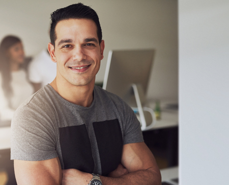 approachable: Close up of confident handsome male worker with folded muscular arms wearing gray short sleeve shirt in small office with other employees behind him