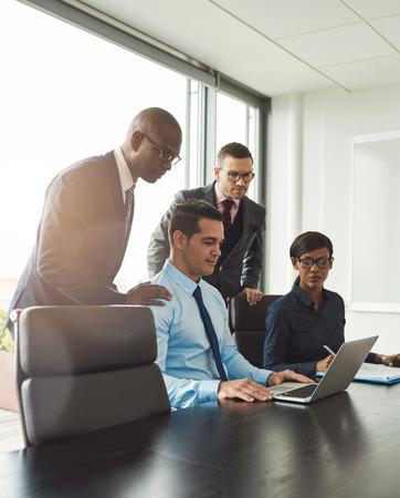 Gruppe von vier unterschiedlichen Männer und eine Frau am Konferenztisch mit hellen Flare in der Ecke von großen Fenster in hellen Büro sitzen Standard-Bild