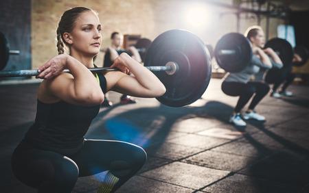 맞는 젊은 여자 리프팅 아가씨는 다른 사람들과 체육관에서 밖으로 작동, 초점을 찾고