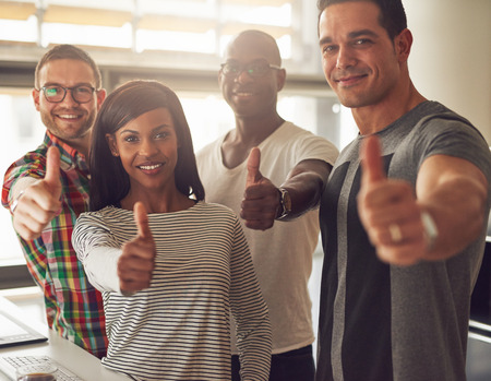 男性と女性のビジネス所有者または承認または彼らのオフィスで何かのように彼らの親指を持ちこたえて従業員の多様なチーム