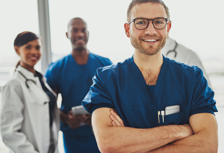doctors: Young doctor in front of team of surgeons and doctors, looking at camera