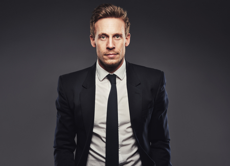 standing businessman: Portrait of handsome business man in dark suit against a grey background