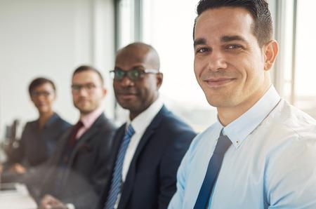 Grupo diverso de cuatro hombres de negocios atractivos sonrientes sentado en la mesa con la ventana de la oficina de nuevo brillante con luz de bengala Foto de archivo