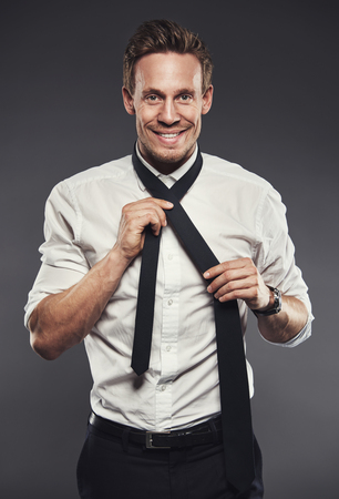 warm shirt: Smiling businessman in a plain white shirt tying his black necktie as he looks at the camera with a warm friendly smile, on grey Stock Photo