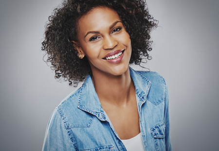 Gorgeous smiling woman in blue denim centered in frame with gray background vignette