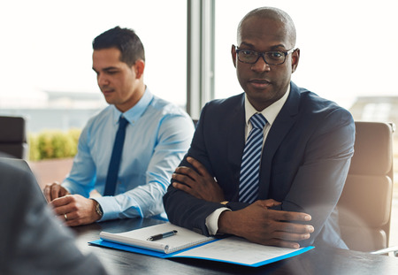Executive multiracial business team having a meeting in the office with focus to a serious middle-aged African American man looking at the camera with folded arms Фото со стока