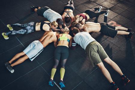Fit junge Menschen konzentrierten sich auf Beplankung in einem Kreis in einem Fitness-Studio Standard-Bild