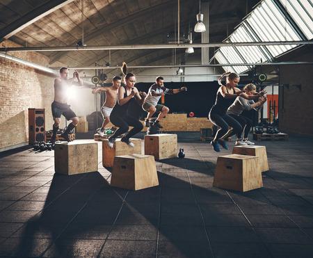 Fit junge Leute Box tut, springt als Gruppe in einem Fitness-Studio