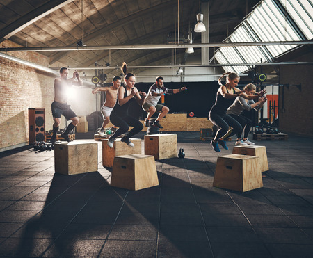Fit young people doing box jumps as a group in a gym Stock Photo
