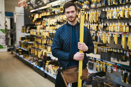 Young carpenter holding a builders level in a hardware store standing in the aisle alongside the merchandise smiling at the camera
