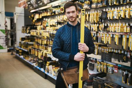 hardware: carpintero joven que sostiene un nivel de constructores en una ferretería de pie en el pasillo junto a la mercancía sonriendo a la cámara