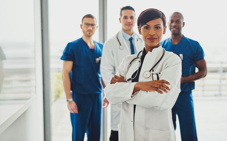 Black female standing in front of team looking at camera, Multiracial medical team