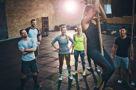 Fit young women climbing a rope in a gym with people on the floor watching