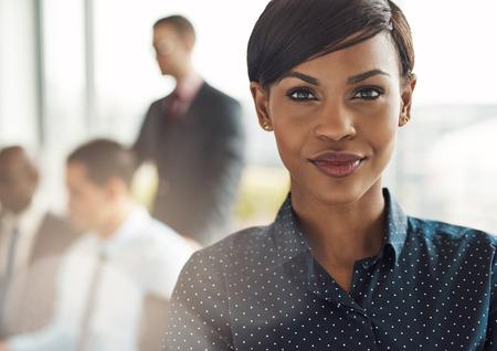 Cerca de sonriente hermosa mujer de negocios con luz bengala sobre el hombro de gran ventana en la oficina con el grupo