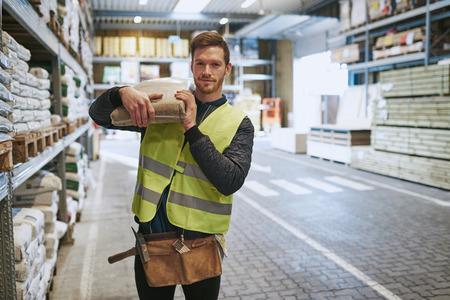 Young handyman selecting a pocket of product in a warehouse standing with the bag over his shoulder smiling at the camera
