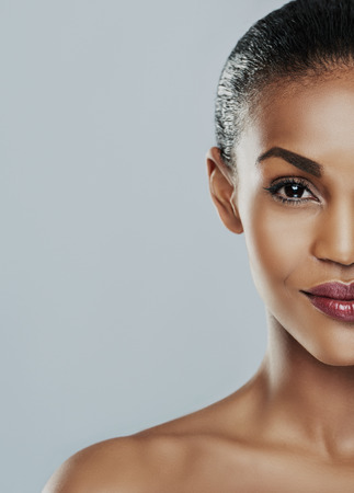 ethnic woman: Half of a beautiful young womans face with perfect skin against a gray background