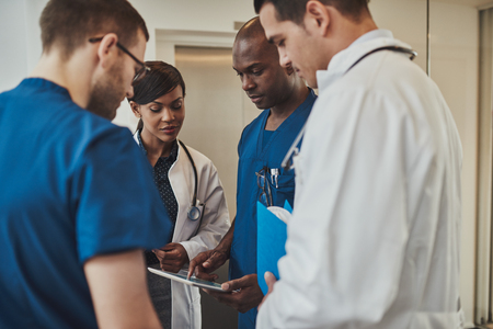 handheld computer: Diverse group of multiracial doctors having an emergency discussion standing grouped closely together looking at a handheld tablet computer