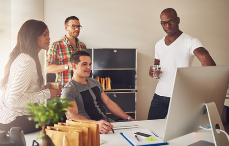 Diverse group of multi-ethnic young adult business people assembled around desk looking at something on their computer monitor Stockfoto