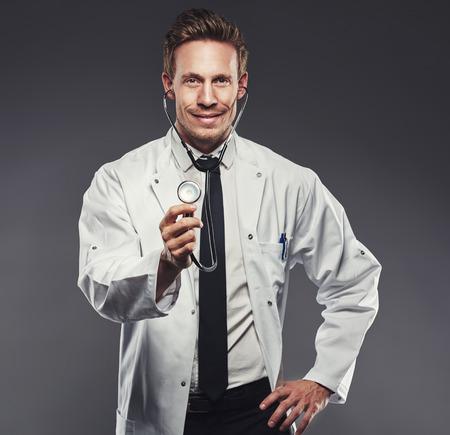 bata blanca: apuesto médico con bata blanca y lazo negro tiene final del estetoscopio sobre un fondo oscuro Foto de archivo