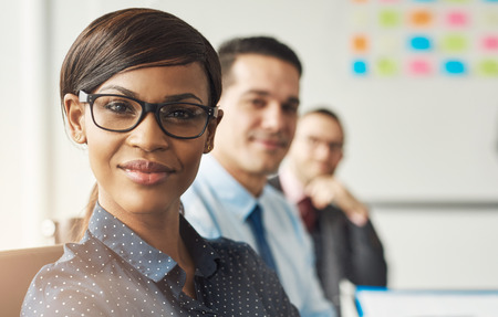 polka dotted: Beautiful smiling business woman wearing eyeglasses and white polka dotted shirt seated with male co-workers at work Stock Photo