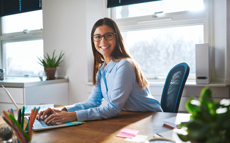 Enthusiastic woman with smile and eyeglasses working at bright sunny desk with windows in background