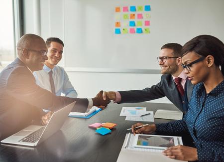 Equipe multirracial, concluindo um acordo de negócios, estendendo a mão para apertar as mãos com sorrisos satisfeitos com foco para uma jovem africana em primeiro plano lendo um tablet pc