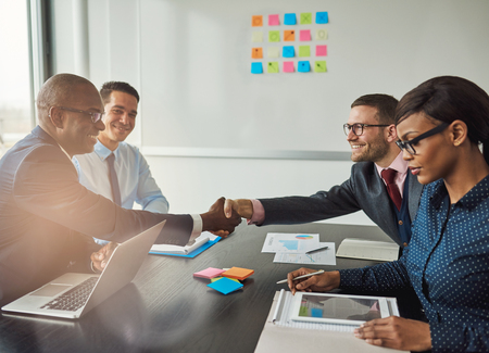 Multiracial team concluding a business agreement reaching across the table to shake hands with pleased smiles with focus to a young African woman in the foreground reading a tablet-pc